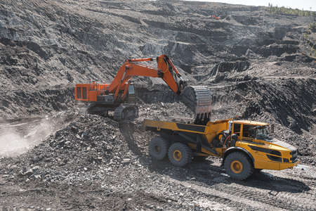 Large quarry dump truck. Loading the rock in dumper. Loading coal into body truck. Production useful minerals. Mining truck mining machinery, to transport coal from open-pit excavator work. Archivio Fotografico