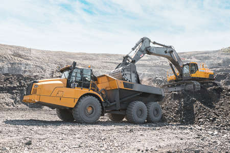 Large quarry dump truck. Loading the rock in dumper. Loading coal into body truck. Production useful minerals. Mining truck mining machinery, to transport coal from open-pit excavator work.