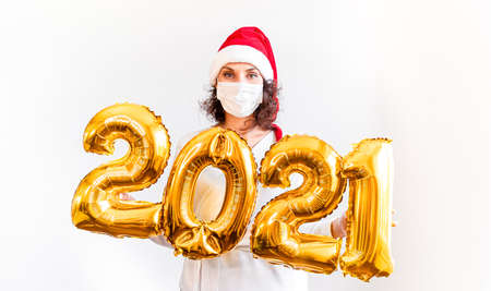 New Year 2021 Gold Number Balloons Covid-19. Beautiful Woman In New Years with red cap. Smiling Girl in at Celebration. Concepts youth lifestyle in medical mask