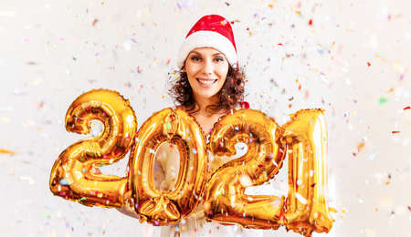 New Year 2021 Gold Number Balloons. Beautiful Woman with Balloons Celebrating new years Eve Party. In New Years red cap. Smiling Girl in Bright Shiny Dress at Celebration