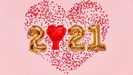 Happy New year 2021 celebration. Bright gold balloons figures, New Year Balloons with glitter stars on pink background. Christmas and new year celebration. Gold foil balloons 2021 gift card