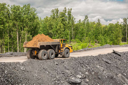 Large quarry dump truck. Big yellow mining truck at work site. Loading coal into body truck. Production useful minerals. Mining truck mining machinery to transport coal from open-pit production