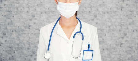 Doctor woman makes stopping hand gesture. Girl Doctor wearing protection face mask against covid-19. Banner panorama medical staff preventive gear about coronavirus. Woman in medical mask stops nCov