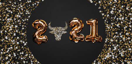Happy New year 2021 celebration. Bright gold balloons figures, New Year Balloons with glitter stars on dark background. Christmas celebration. Gold foil balloons With symbol of the year of the bull Foto de archivo