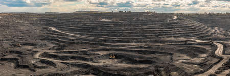 Panoramic aerial view of coal mine. Open pit mine industry, big yellow mining truck for coal quarry. Open coal mining anthracite mining. Pit on coal mining by open way. Rock loading in trucks Foto de archivo