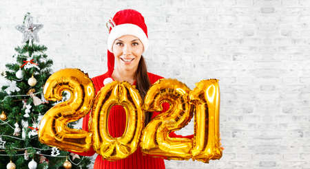 New Year 2021 Gold Balloons. Young woman in Santa Claus hat having smiling holding in hand 2021. Girl in red hat and red Dress stands on background of Christmas tree. Concept Christmas celebration