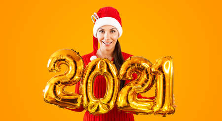 New Year 2021 Gold Balloons. Young woman in Santa Claus hat having smiling holding in hand 2021. Girl in red hat and red Dress stands on bright orange background. Concept Christmas celebration