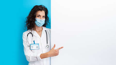 Doctor in face mask on bright color background make gesture hand. Girl wearing protection face mask covid-19. Banner medical staff preventive gear about coronavirus. Woman in medical mask covid-2019