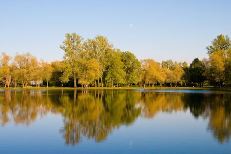 Park in the autumn. Reflexion in water, trees, the sky.
