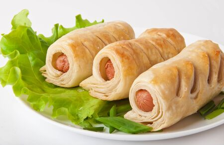sausage in the dough on a plate with greens photo