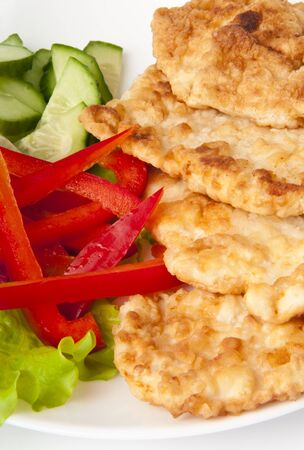 Appetizing fried chicken nuggets with cucumber and pepper on salad leaves  Close-up  Selective focus  photo