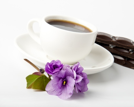 cup of coffee, chocolate and violets on a white table Stock Photo