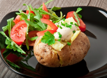 Baked potato filled with sour cream and arugula photo
