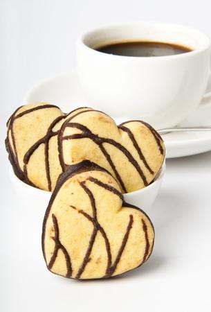 galletas: taza de café y galletas en un chocolate con forma de corazón Foto de archivo
