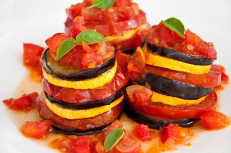 Delicious Ratatouille on a white plate decorating with a leaf of basil