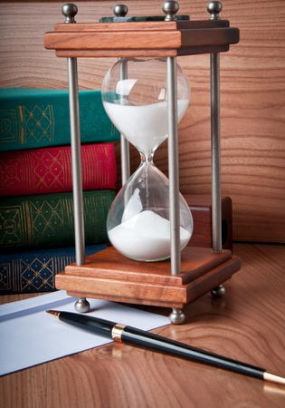 Hourglasses and book on a wooden table photo