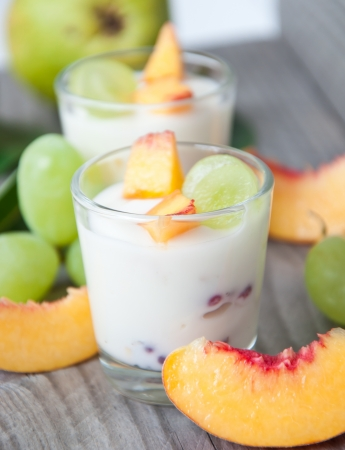 Fresh peach and grape yogurt in glass