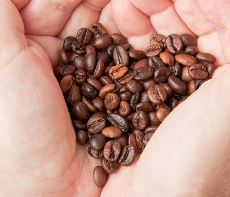 Heart of coffee grains in hands photo