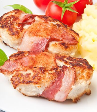 grilled chicken patties wrapped strips of bacon and mashed potatoes photo
