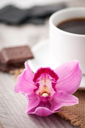 desayuno romantico: taza de caf�, chocolate y orqu�dea sobre fondo de madera Foto de archivo