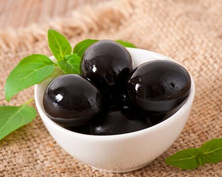 Black olives on a wooden table Stock Photo - 18429481