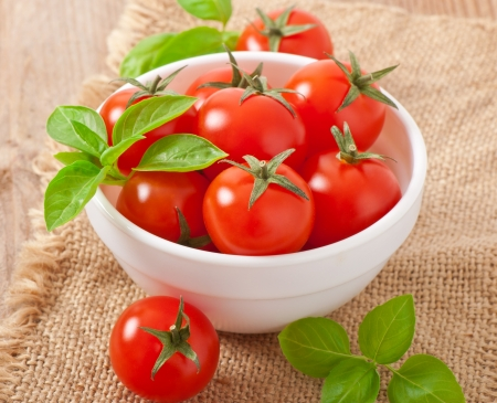 Cherry tomatoes in a bowl with basil photo