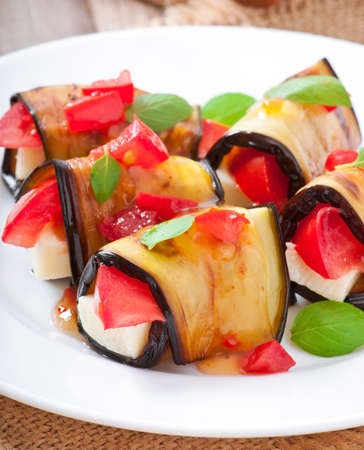 Eggplant rolls stuffed with cheese with a slice of tomato photo