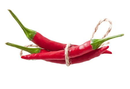 Red hot chili peppers tied with rope isolated on white background photo