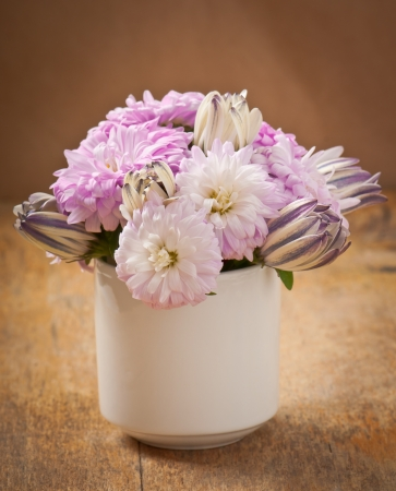 Beautiful aster flower bouquet on wooden table photo