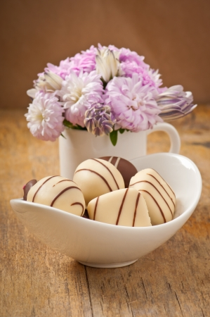 Beautiful aster flower bouquet and chocolates on wooden table photo