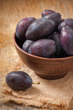 Plums in bowl on wooden table photo