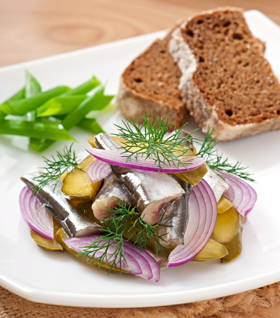 herring salad with pickled cucumbers and onions photo
