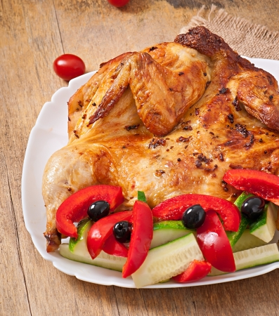 small grilled chicken with vegetables on a white dish photo