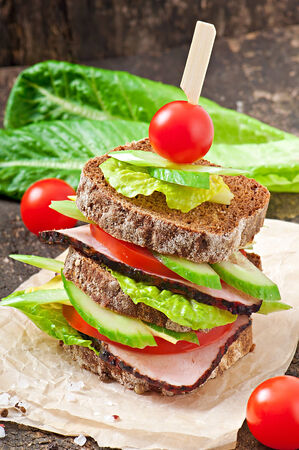 Sandwich with ham and fresh vegetables on a wooden background photo