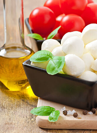 Mozzarella, tomatoes and fresh basil leaves on wooden background photo