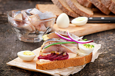 Sandwich of rye bread with herring, beets, onions and egg photo