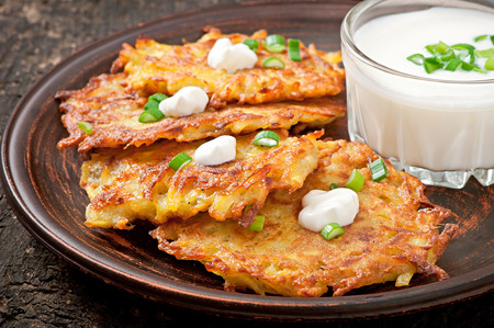 fritter: Fried potato pancakes on the old wooden background