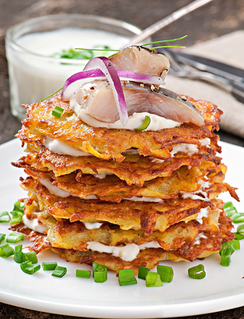 Fried potato pancakes with herring on the old wooden background photo