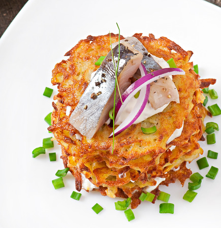 Fried potato pancakes with herring on white background photo