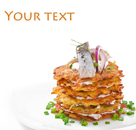 Fried potato pancakes with herring on white  photo