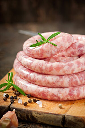 Fresh raw sausage on the old wooden background photo
