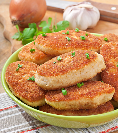 Chicken cutlets in a green bowl photo