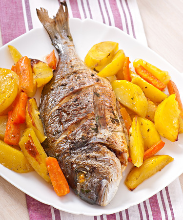 Dorada baked with potatoes photo
