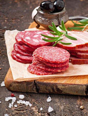Assorted deli meats, rosemary and pepper photo