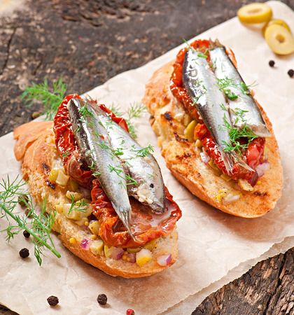 Crostini with anchovies, olives and sun-dried tomatoes photo