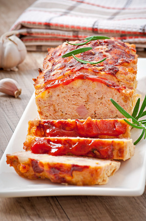 Homemade ground meatloaf with ketchup and rosemary photo