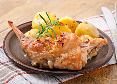 Oven Baked rabbit legs with potatoes and rosemary photo
