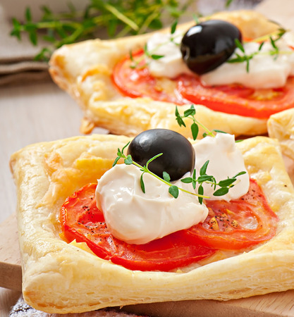 Mini puffs with tomatoes, cheese and olives photo