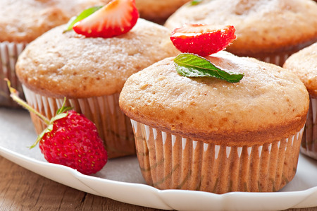 Strawberry muffin on a white plate with a fresh strawberry photo