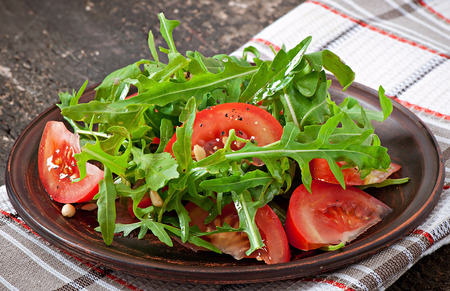 Salad with arugula, tomatoes and pine nuts photo